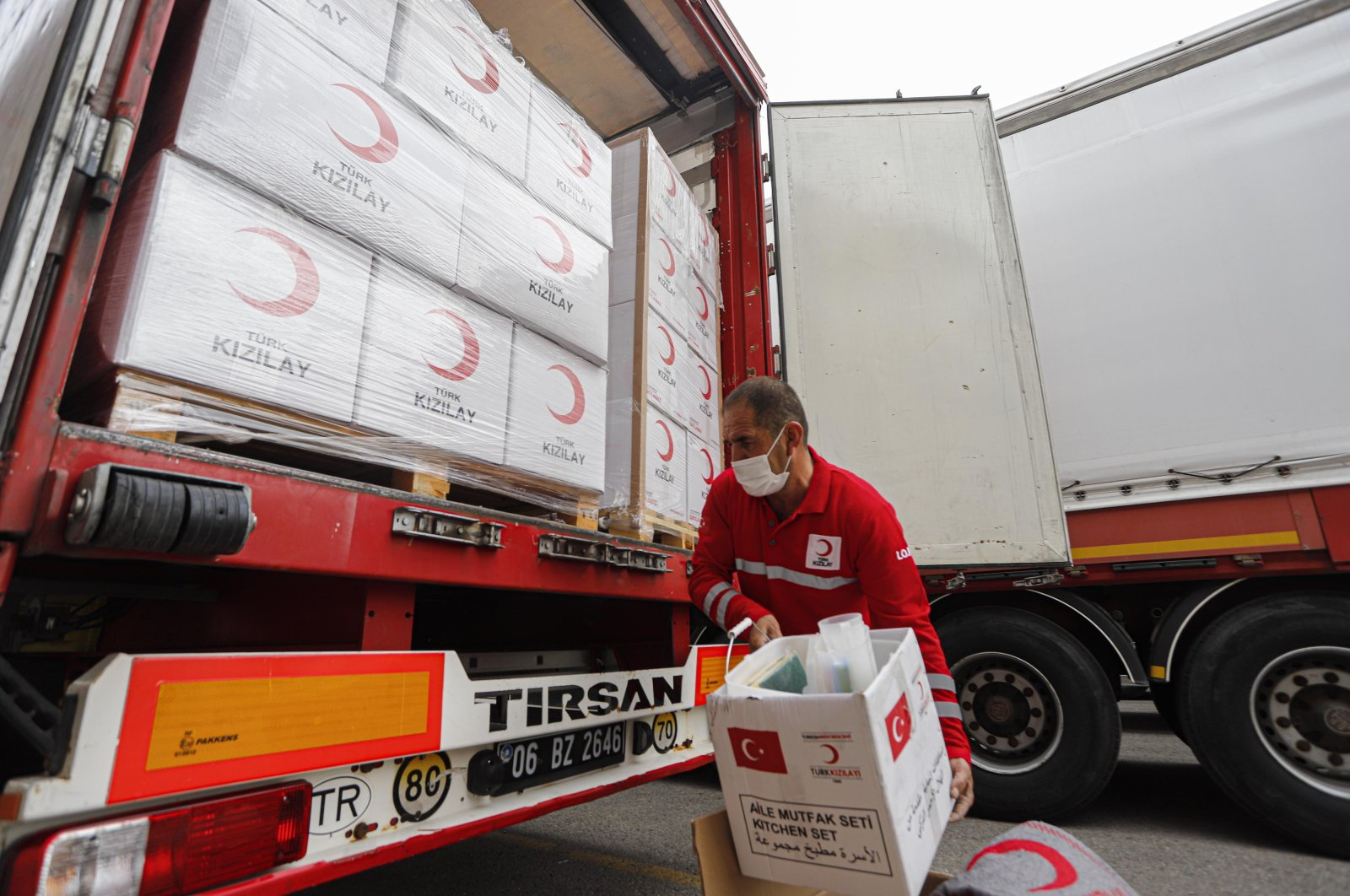A Turkish Red Crescent employee loads humanitarian aid boxes into a truck that will soon depart for Azerbaijan, in Ankara, Turkey, Oct. 9, 2020. (DHA Photo)