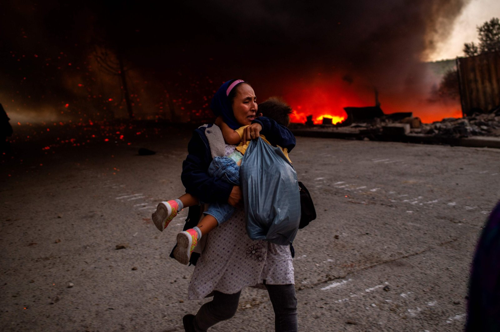 A migrant holds a girl as they flee a fire burning in the Moria camp on the island of Lesbos, Greece, Sept. 9, 2020. (AFP Photo)