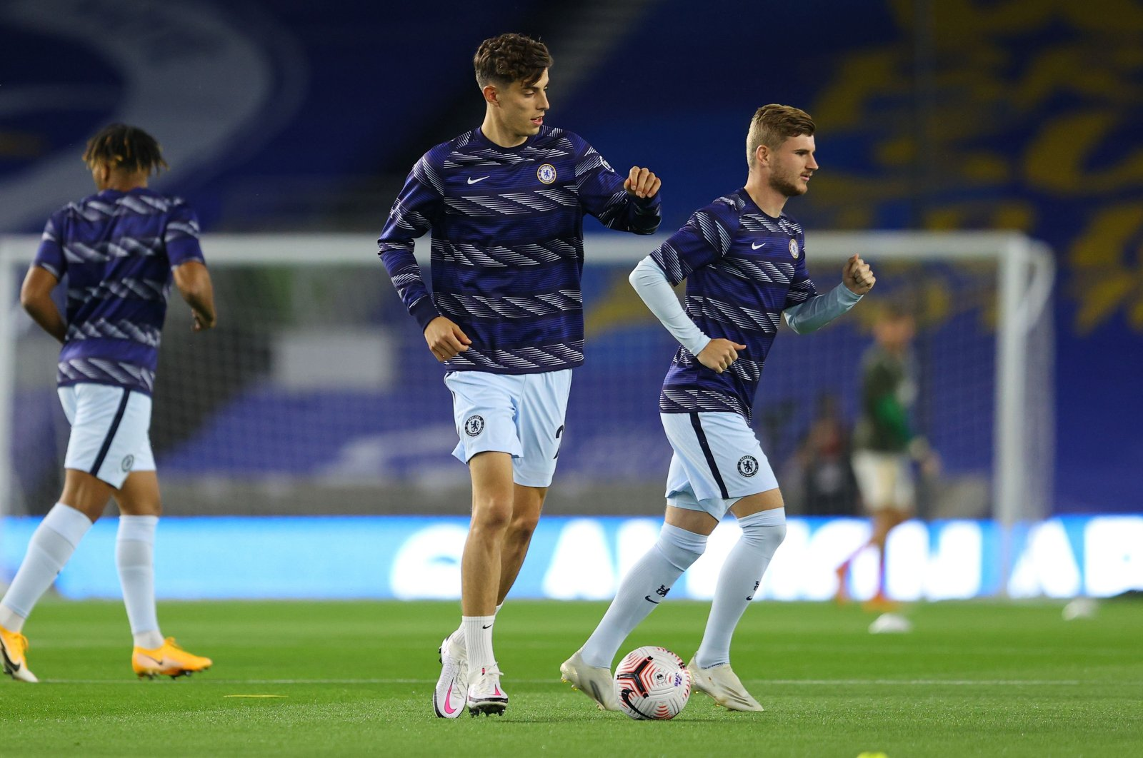 Chelsea's midfielder Kai Havertz (C) and forward Timo Werner (R), signed for a combined $160 million, warm up ahead of the Premier League football match between Brighton & Hove Albion and Chelsea at the American Express Community Stadium in Brighton, England, Sept. 14, 2020. (AFP Photo)