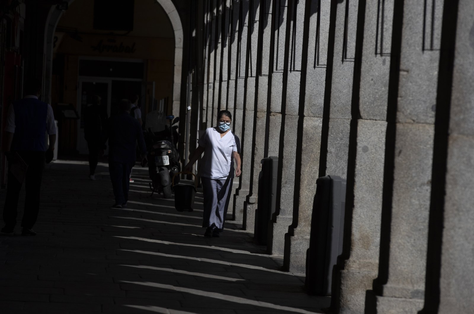 A cleaner wearing a face mask to prevent the spread of coronavirus works at the Plaza Mayor square in downtown Madrid, Spain, Friday, Oct. 9, 2020. (AP Photo)