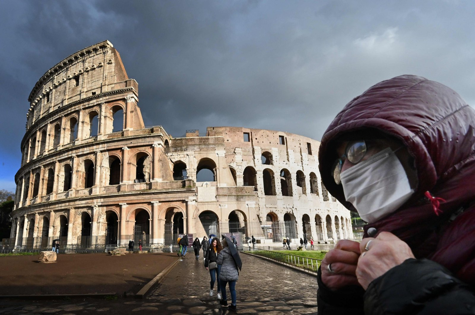 A man wearing a protective mask passes by the Coliseum monument in Rome amid fear of the Covid-19 pandemic, March 7, 2020. (AFP Photo)