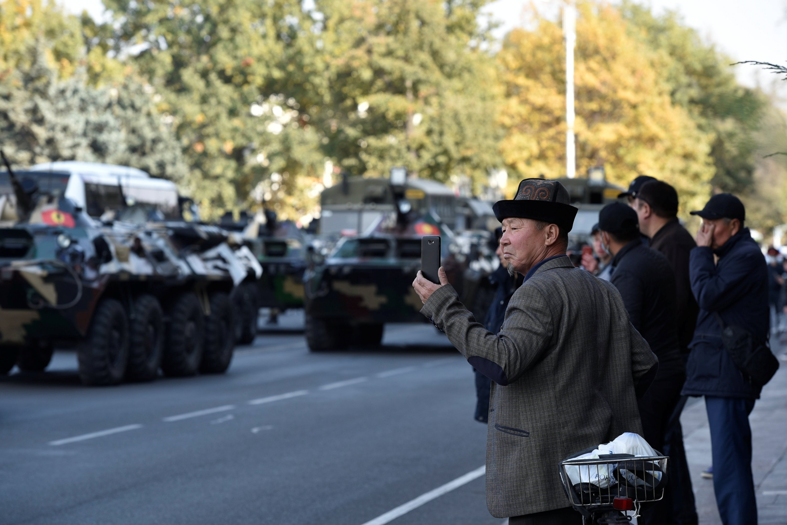 Local residents watch as Kyrgyz military vehicles drive along the street after President Sooronbai Jeenbekov declared a state of emergency in the capital and ordered troops to be deployed there, in Bishkek, Kyrgyzstan Oct. 10, 2020. (Reuters Photo)