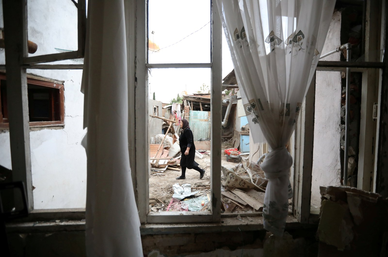 A woman walks past a house damaged by recent Armenian shelling during a military conflict over Nagorno-Karabakh, in the city of Ganja, Azerbaijan, Oct. 6, 2020. (Reuters Photo)