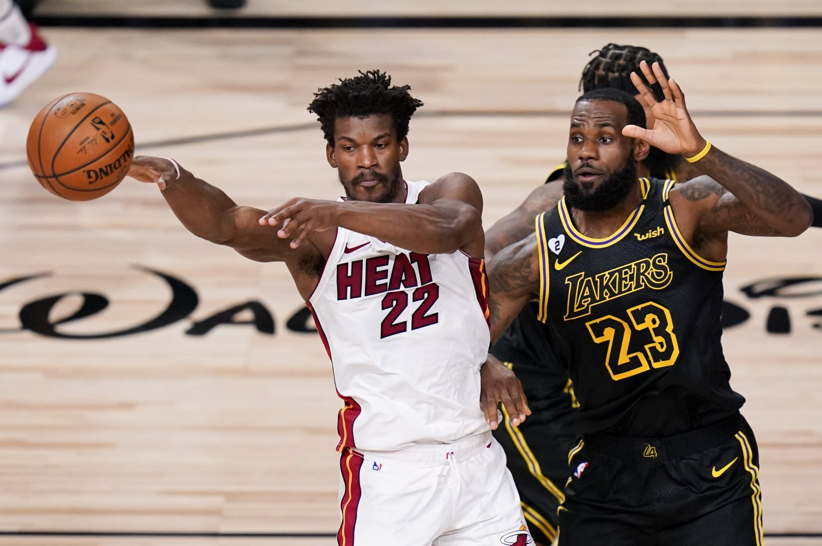 Miami Heat forward Jimmy Butler, left, passes around Los Angeles Lakers forward LeBron James during the first half in Game 5 of basketball's NBA Finals Friday, Oct. 9, 2020, in Lake Buena Vista, Florida. (AP Photo)