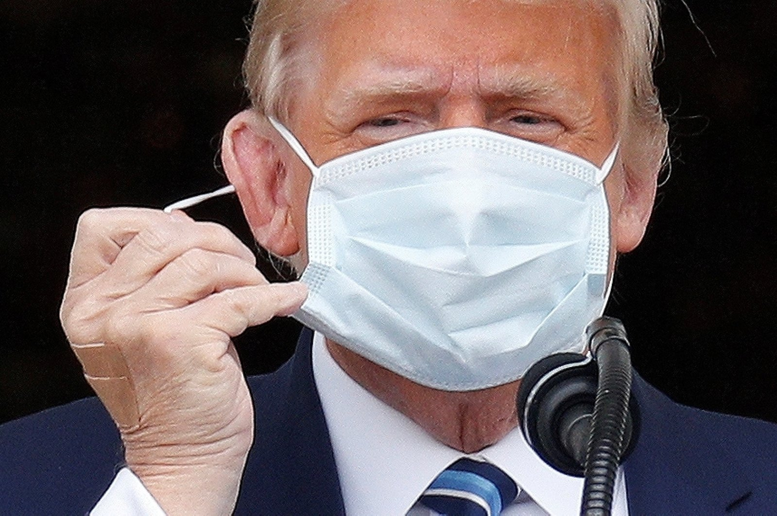 """U.S. President Donald Trump takes off his face mask as he comes out on a White House balcony to speak to supporters gathered on the South Lawn for a campaign rally that the White House is calling a """"peaceful protest"""" in Washington, U.S., Oct. 10, 2020.  (Reuters Photo)"""