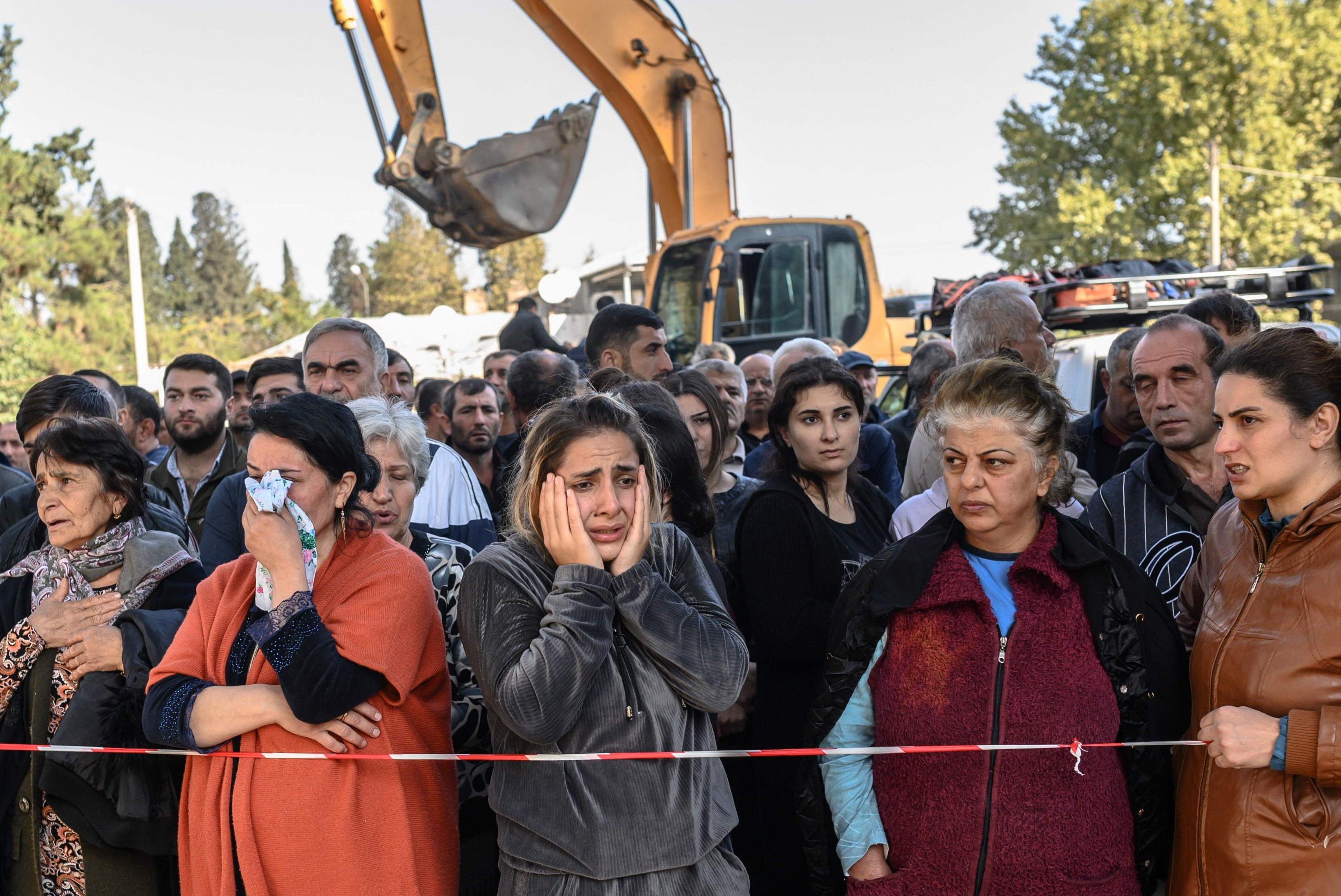 Azerbaijani people stand behind caution tape as rescuers search for victims or survivors at the blast site hit by an Armenian rocket in the city of Ganja, Azerbaijan, on Oct.11, 2020. (AFP)