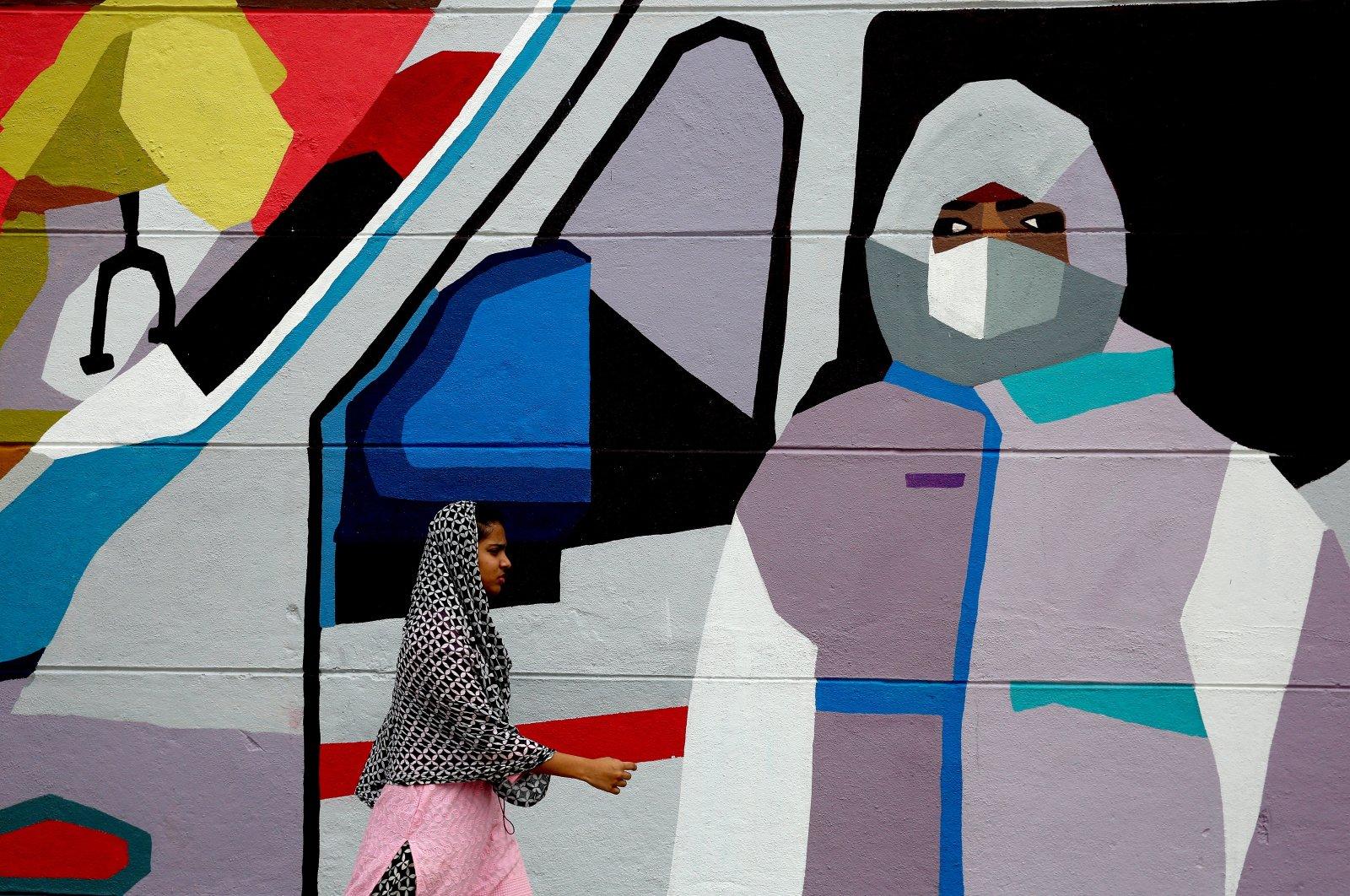 "Indian people walk past graffiti depicting ""The story of the coronavirus pandemic'' to create awareness among people, Bangalore, Oct. 10, 2020. (EPA Photo)"