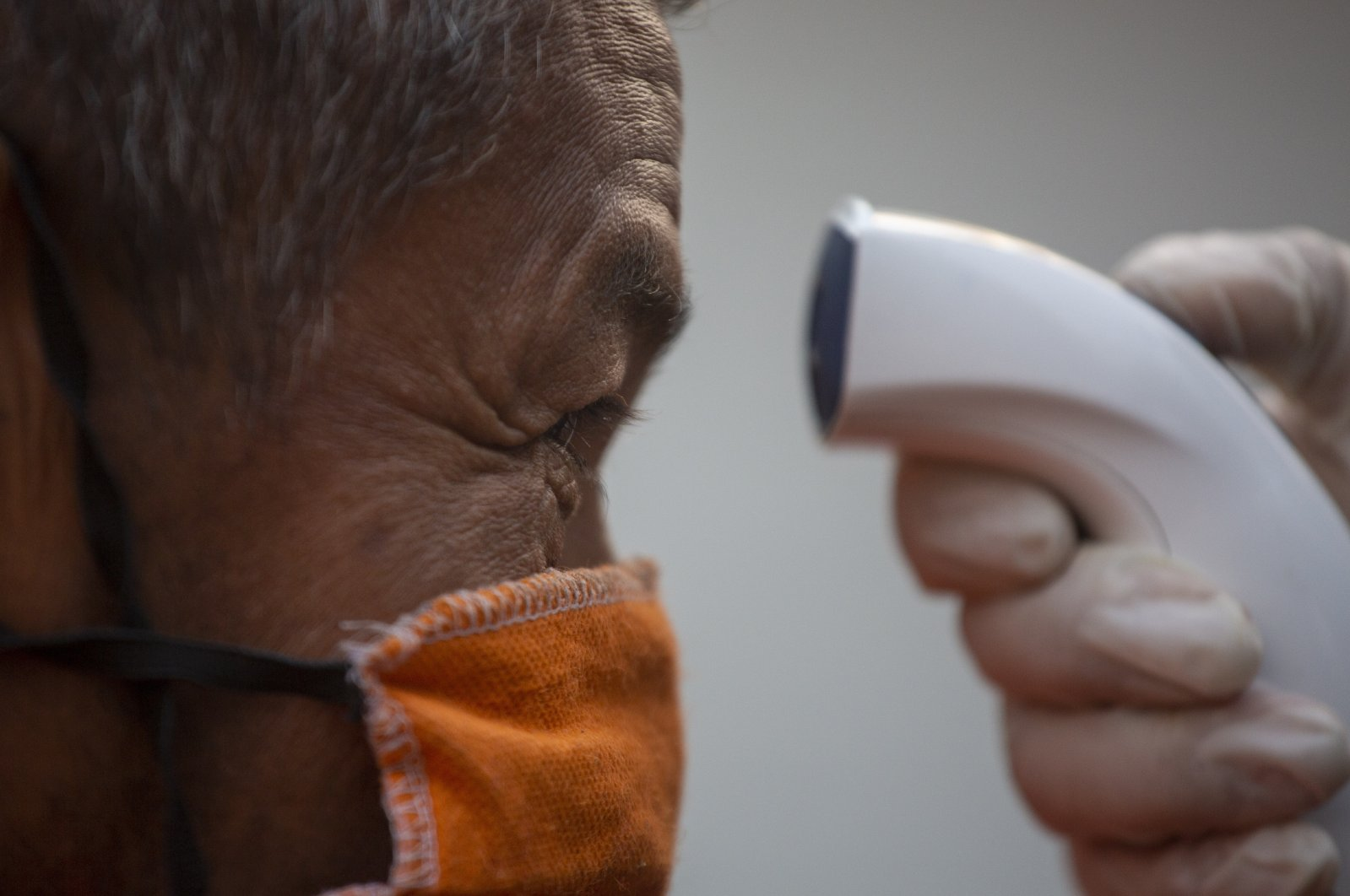 A volunteer uses a no-touch forehead thermometer to check the temperature of a man at a temporary shelter for homeless and unemployed persons in Guatemala City, Guatemala, April 28, 2020. (AP Photo)
