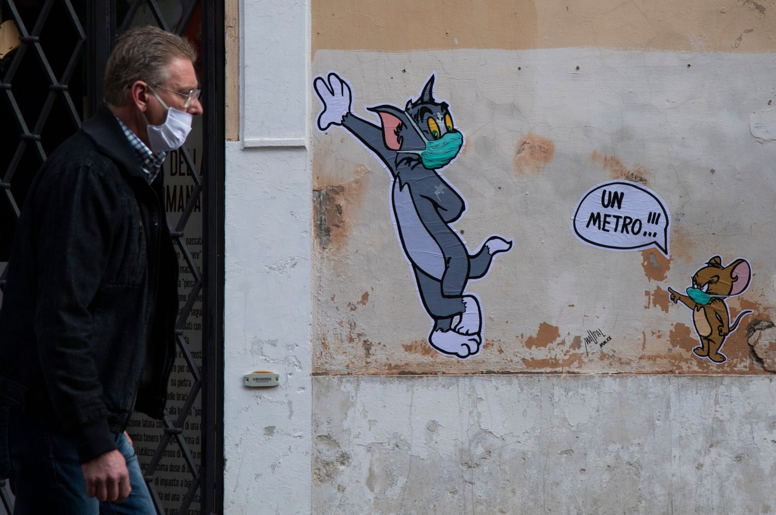 A man wearing a mask to protect against the coronavirus spread walks past a mural in Rome, April 29, 2020. (AFP Photo)
