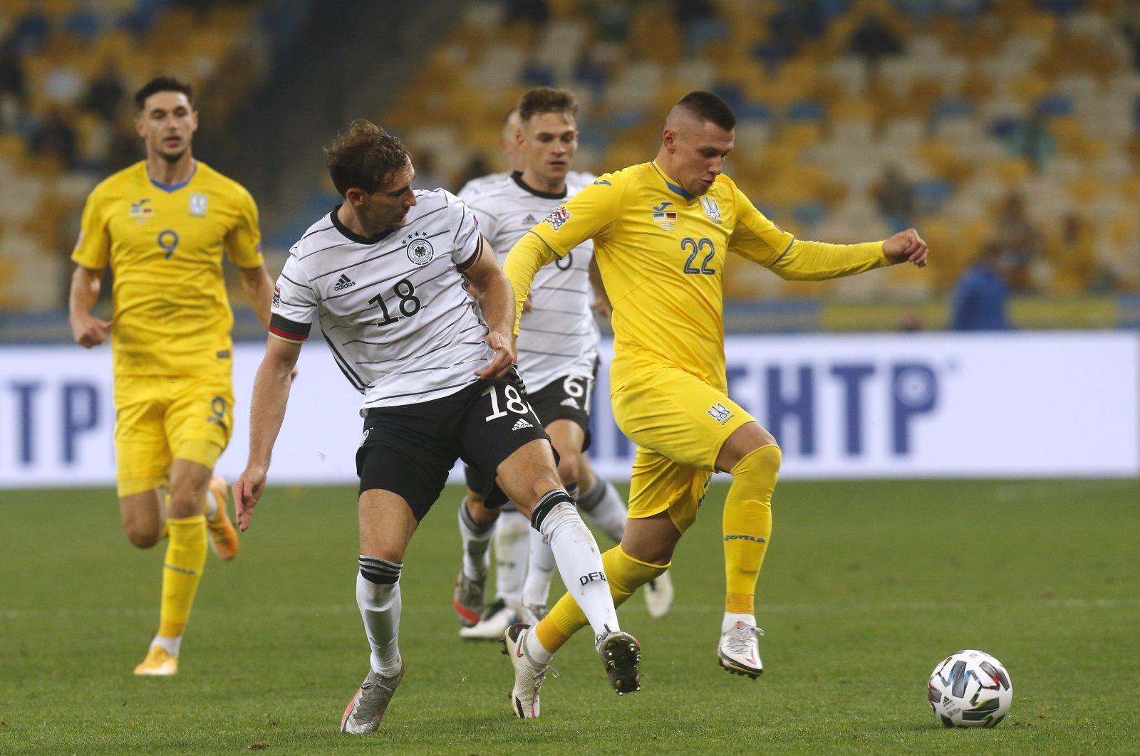 Germany's Leon Goretzka and Ukraine's Oleksandr Zubkov challenge for the ball, in Kyiv, Ukraine, Oct. 10, 2020. (AP Photo)