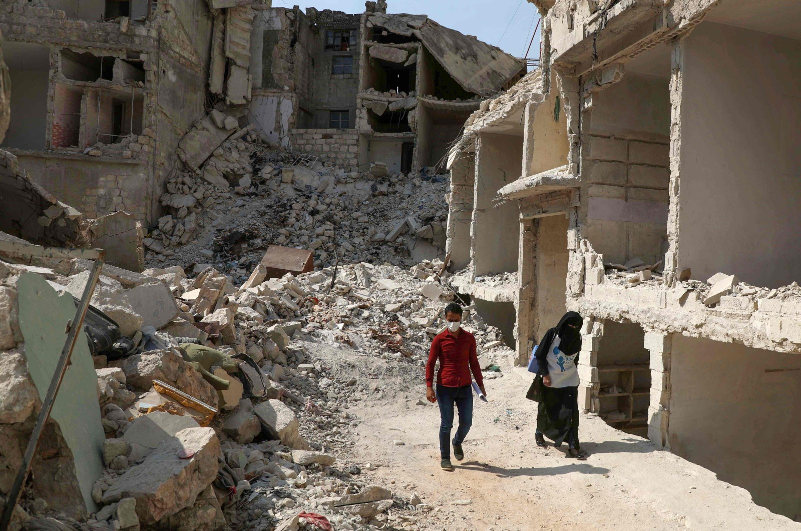 A team of two Syrian medics, taking part in a vaccination campaign against the polio disease, go door to door in the ravaged town of Ariha in the opposition-held northwestern Idlib province, to give vaccine drops to children, Oct. 10, 2020. (AFP Photo)