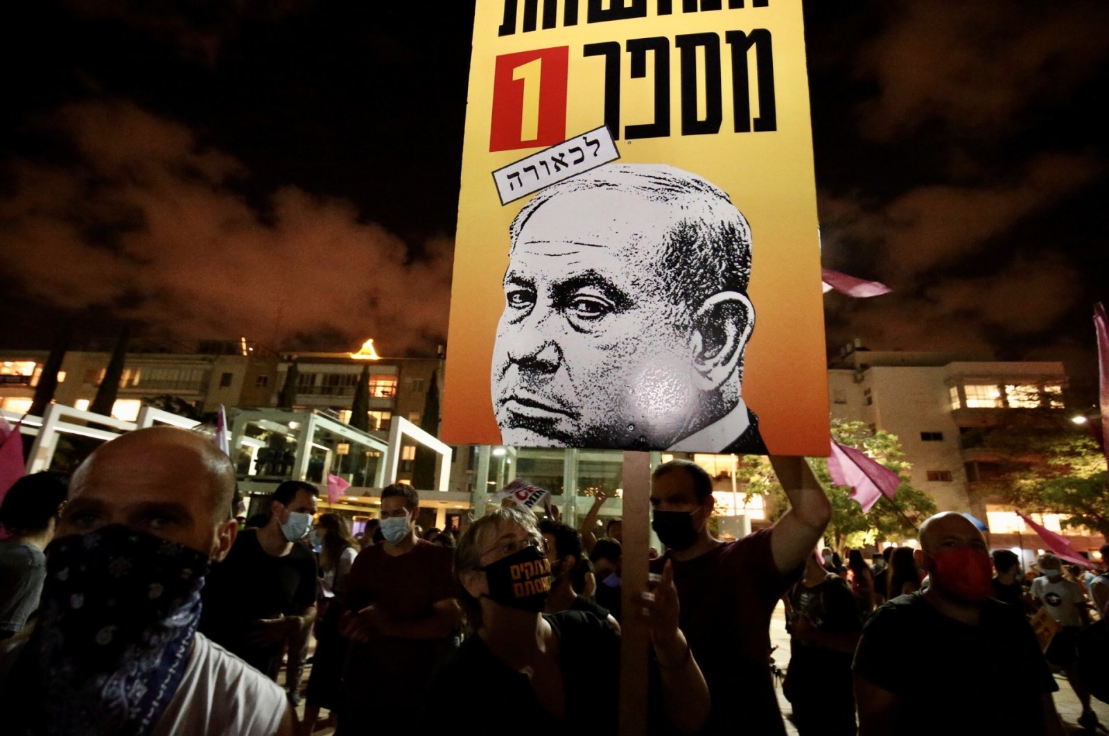 Israeli protesters lift placards during a demonstration against Prime Minister Benjamin Netanyahu, Tel Aviv, Oct. 10, 2020. (AA Photo)