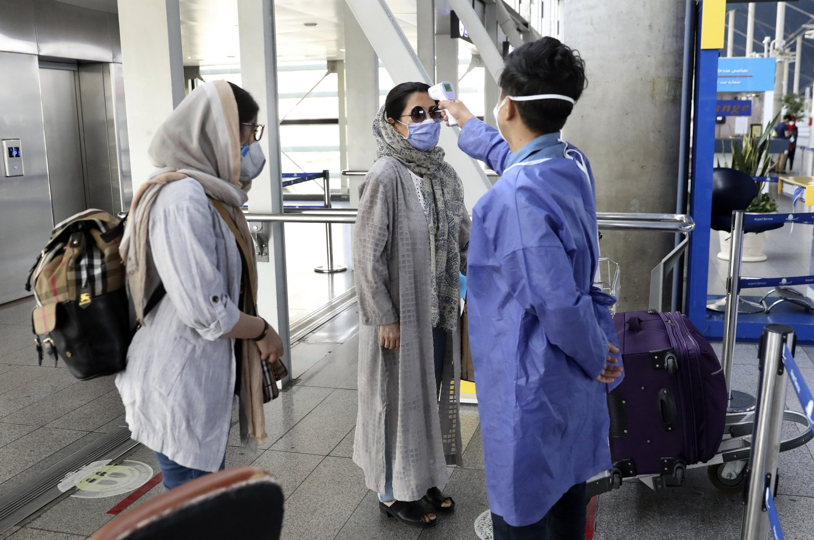 A health worker (R) checks the temperature of passengers to help prevent the spread of the coronavirus upon arrival at the departure terminal of Tehran's Imam Khomeini airport, Iran, July 17, 2020. (AP Photo)