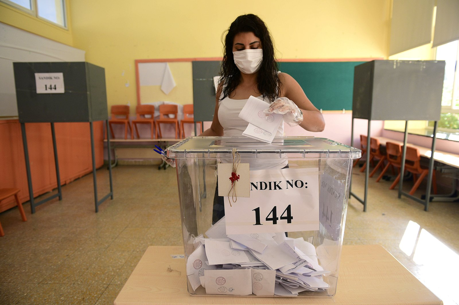 A woman casts her ballot at a polling station during the Turkish Cypriots election for a new leader in the Turkish occupied area in the north part of the divided capital Nicosia, Cyprus, Oct. 11, 2020. (AP)