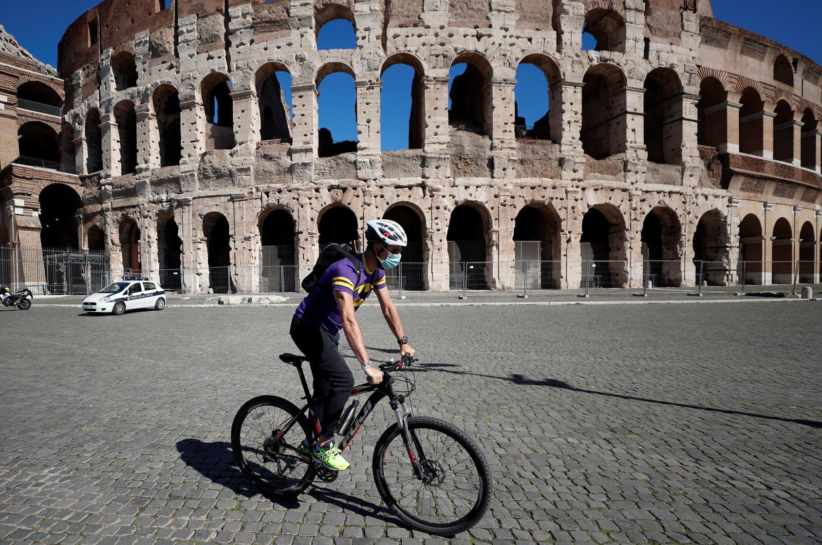 A man wearing a protective face mask cycles past the Colosseum as local authorities in the Italian capital Rome ordered face coverings to be worn at all times outdoors, in an effort to counter the spread of the coronavirus disease (COVID-19), in Rome, Italy on Oct. 8, 2020. (Reuters Photo)