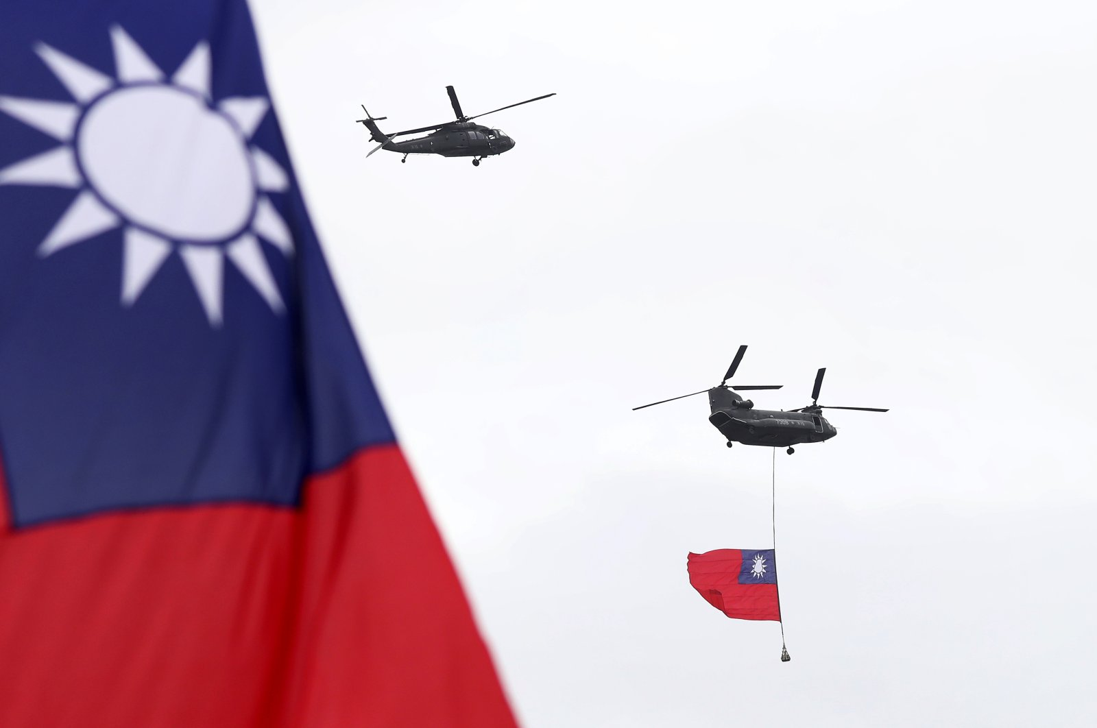 Helicopters fly over the President's Office with a Taiwan national flag during the National Day celebrations in Taipei, Taiwan, Oct. 10, 2020. (AP Photo)