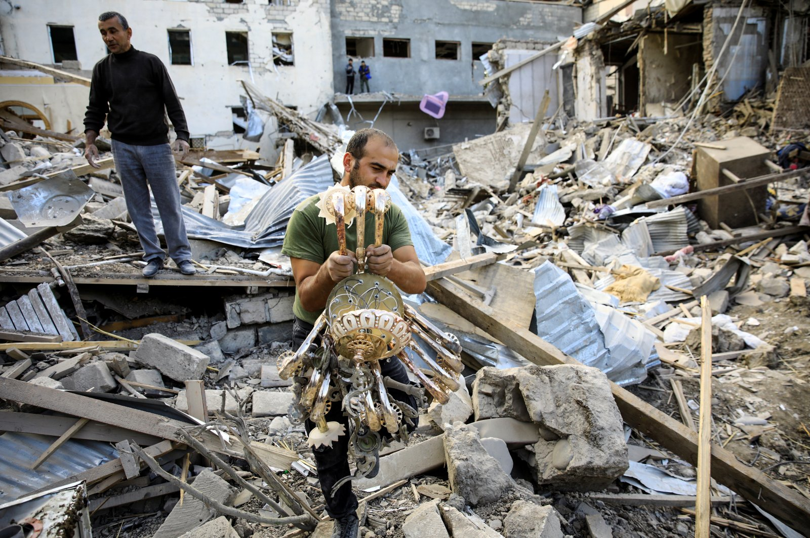 An Azerbaijani man carries a chandelier away from the ruins of a blast site hit by an Armenian rocket over the conflict in the occupied region of Nagorno-Karabakh in the city of Ganja, Azerbaijan, Oct. 11, 2020. (Reuters Photo)