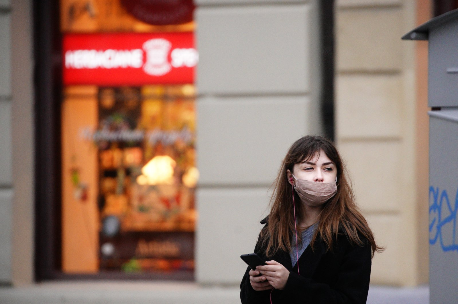 A woman wearing a face mask uses her mobile phone while waiting at a bus stop in Warsaw, Poland on October 2, 2020. (Reuters Photo)