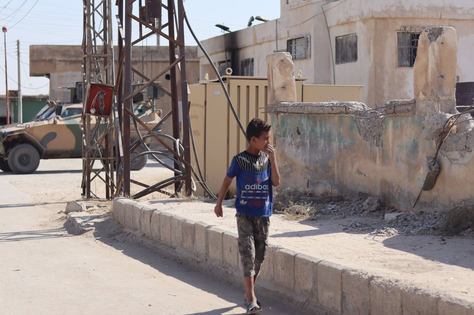 A Syrian boy walks along the streets of northern Tal Abyad where buildings have been damaged to a large extent by terrorist organizations, Oct. 11, 2020. (Dilara Aslan)