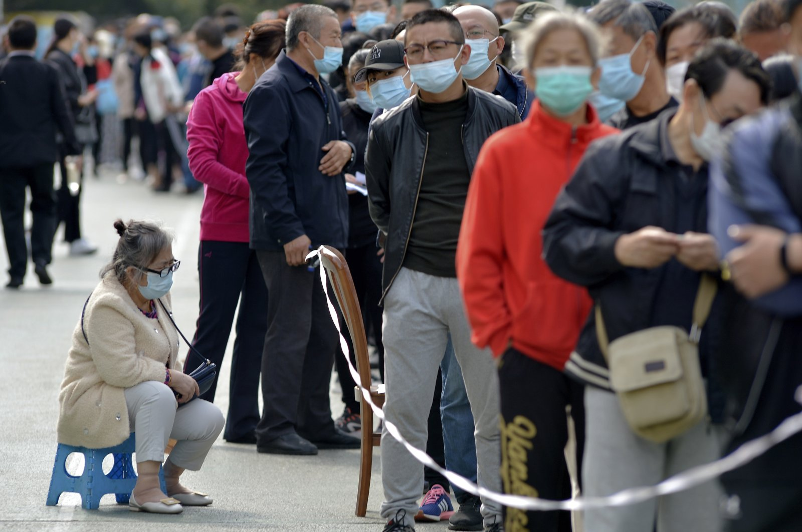 A woman wearing a mask to help curb the spread of the coronavirus sits on a stool as masked residents line up for COVID-19 tests near the residential area, Qingdao in east China's Shandong province, Oct. 12, 2020. (AP Photo)