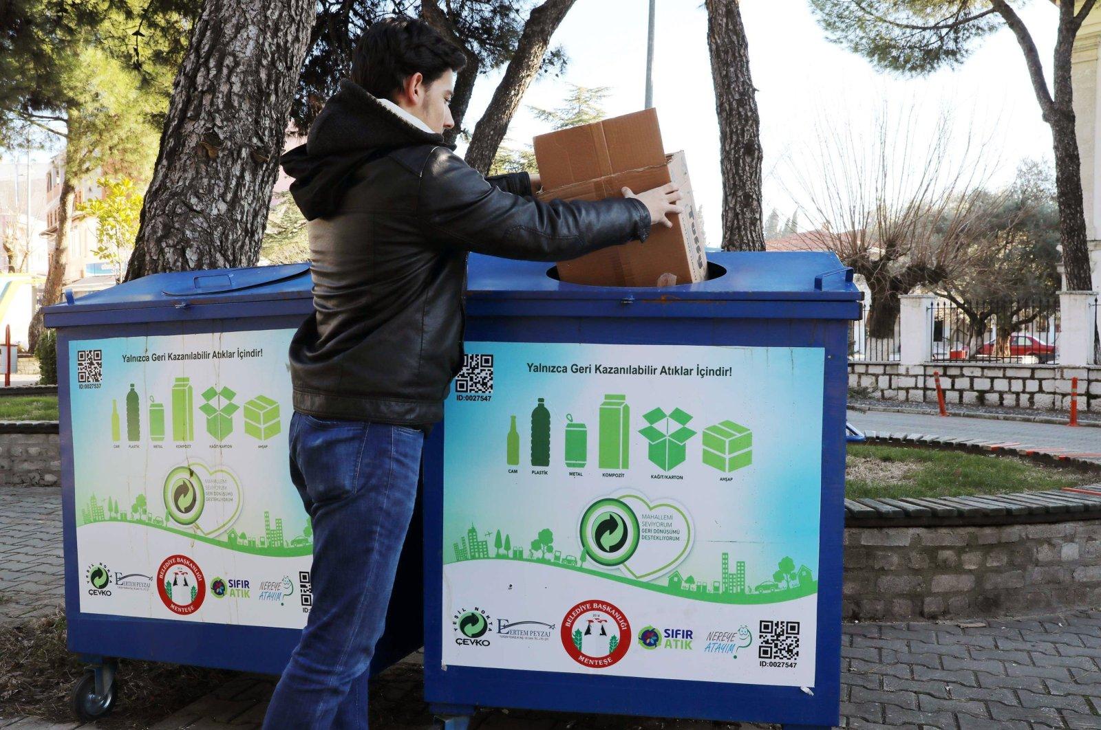 A man dumps a cartoon box in a zero-waste dumpster in Menteşe district, in Muğla, southwestern Turkey, Oct. 10, 2020. (İHA Photo)