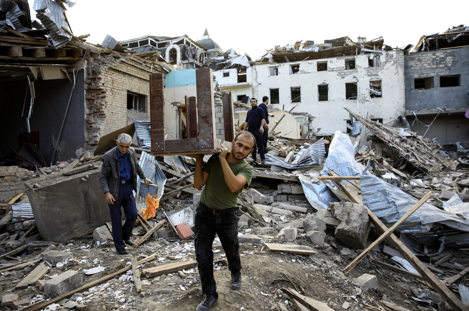 A man carries a table away from ruins at a blast site hit by a rocket during the fighting over the breakaway region of Nagorno-Karabakh in the city of Ganja, Azerbaijan on Oct. 11, 2020. (Reuters Photo)