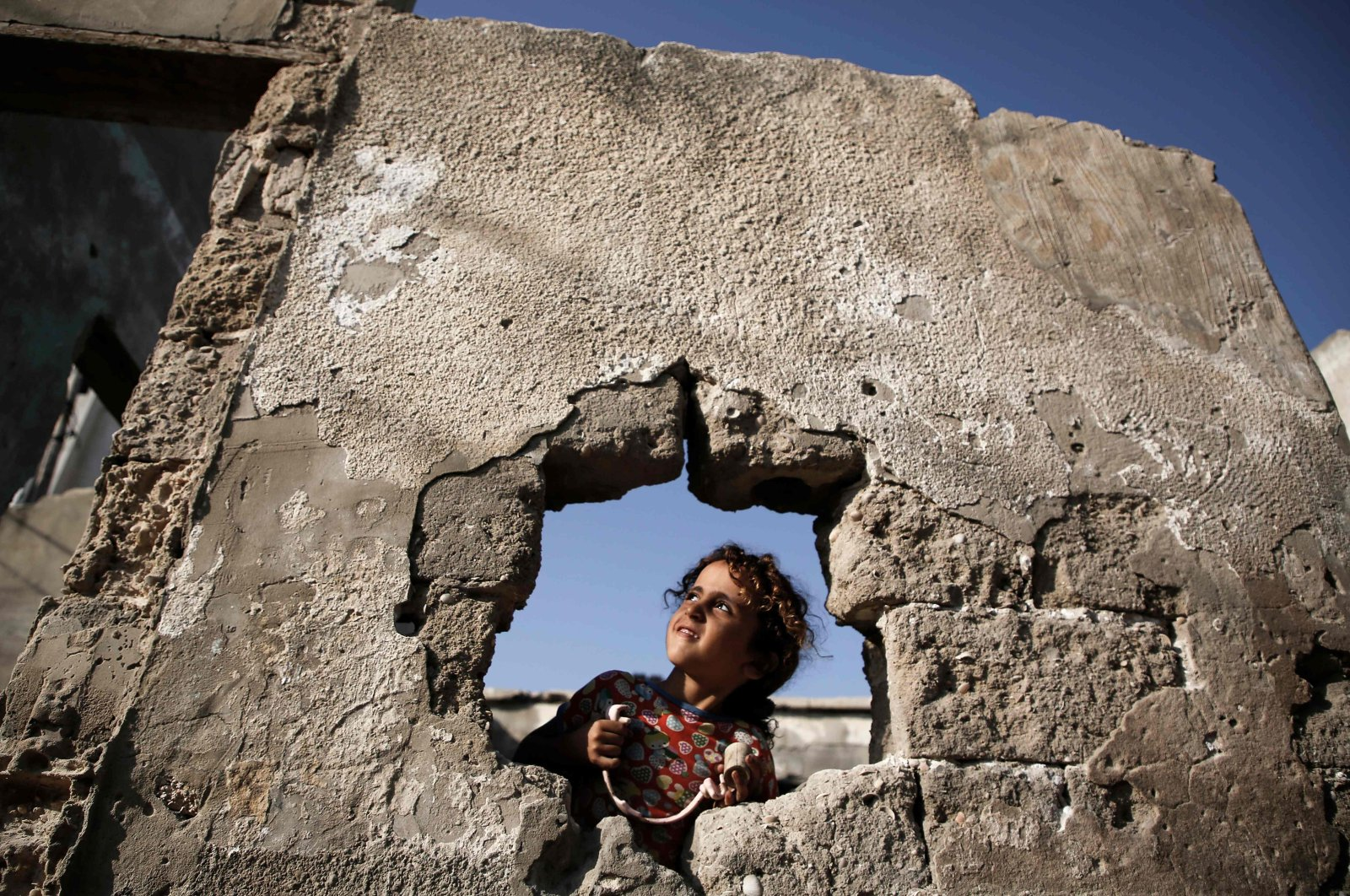 A Palestinian girl is pictured behind a whole at her destroyed family's house, Gaza City, Oct. 8, 2020. (AFP Photo)