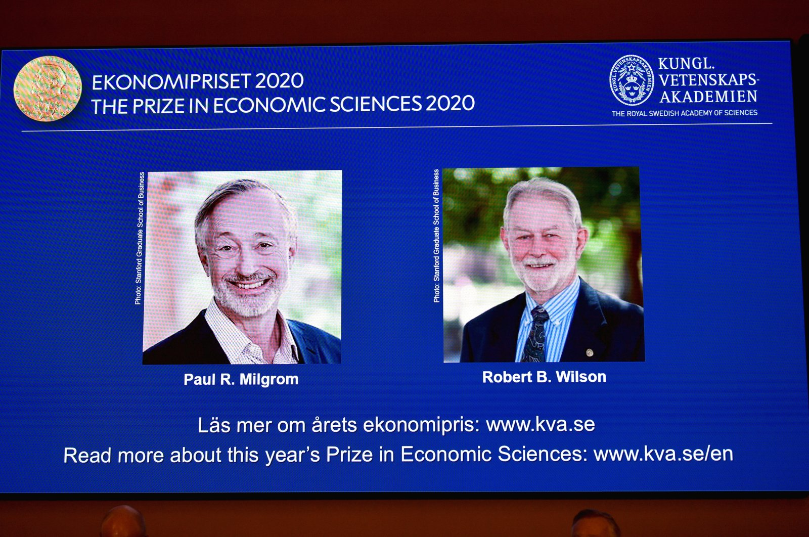 Pictures of the winners of the 2020 Nobel Prize in Economics, Paul R. Milgrom and Robert B. Wilson, are displayed on a screen at a news conference in Stockholm, Sweden, Oct. 12, 2020. (TT News Agency via Reuters)