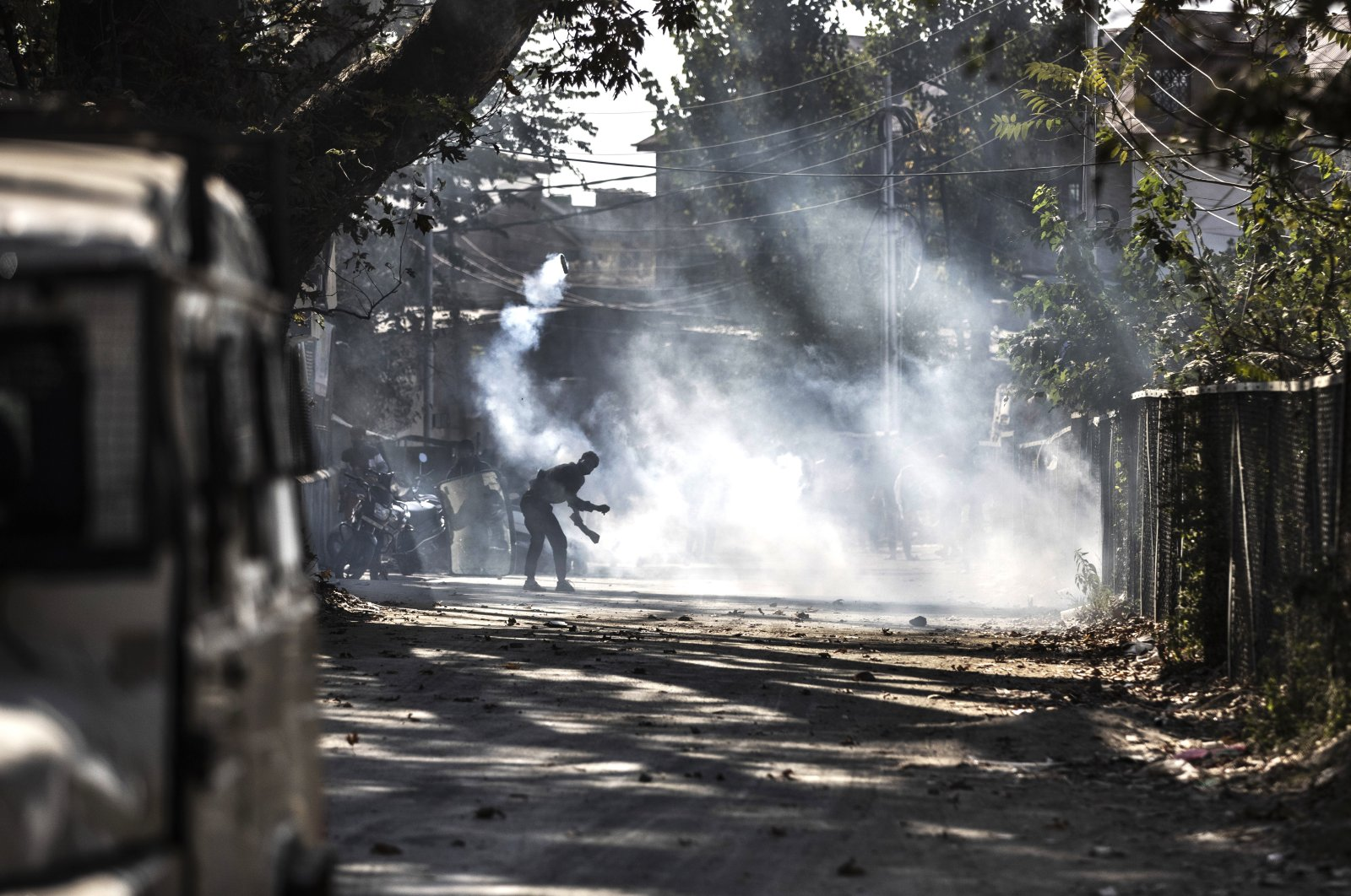 A Kashmiri protester throws an exploded tear smoke shell on Indian forces during a clash following the killing of two suspected rebels in a gunfight with government forces in Srinagar, Kashmir, Oct. 12, 2020. (AP Photo)