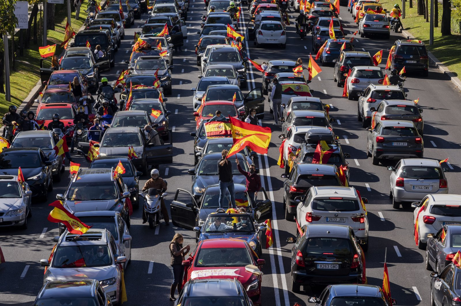 People wave Spanish flags during a drive-in protest organized by Spain's far-right Vox party against the Spanish government's handling of the nation's coronavirus outbreak din Madrid, Spain, Monday, Oct. 12, 2020. (AP Photo)