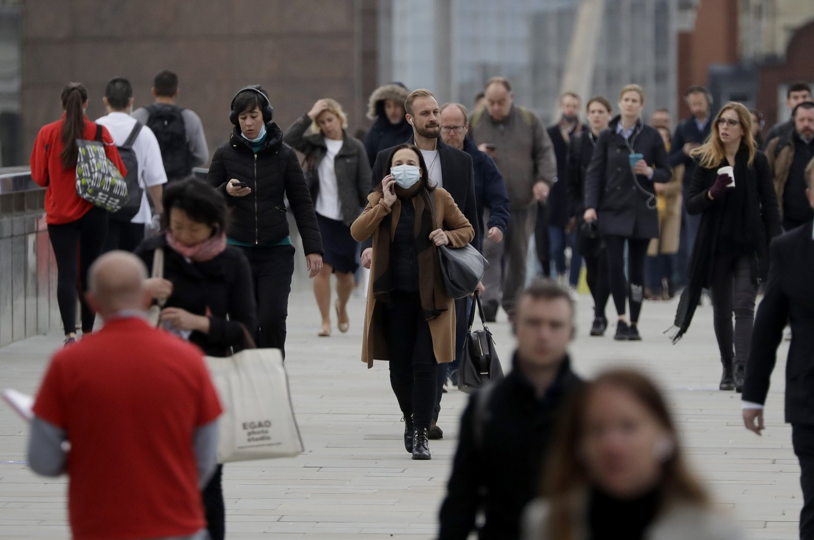 Commuters walk across London Bridge during the morning rush hour toward the offices in London's financial district, Oct. 12, 2020. (AP Photo)