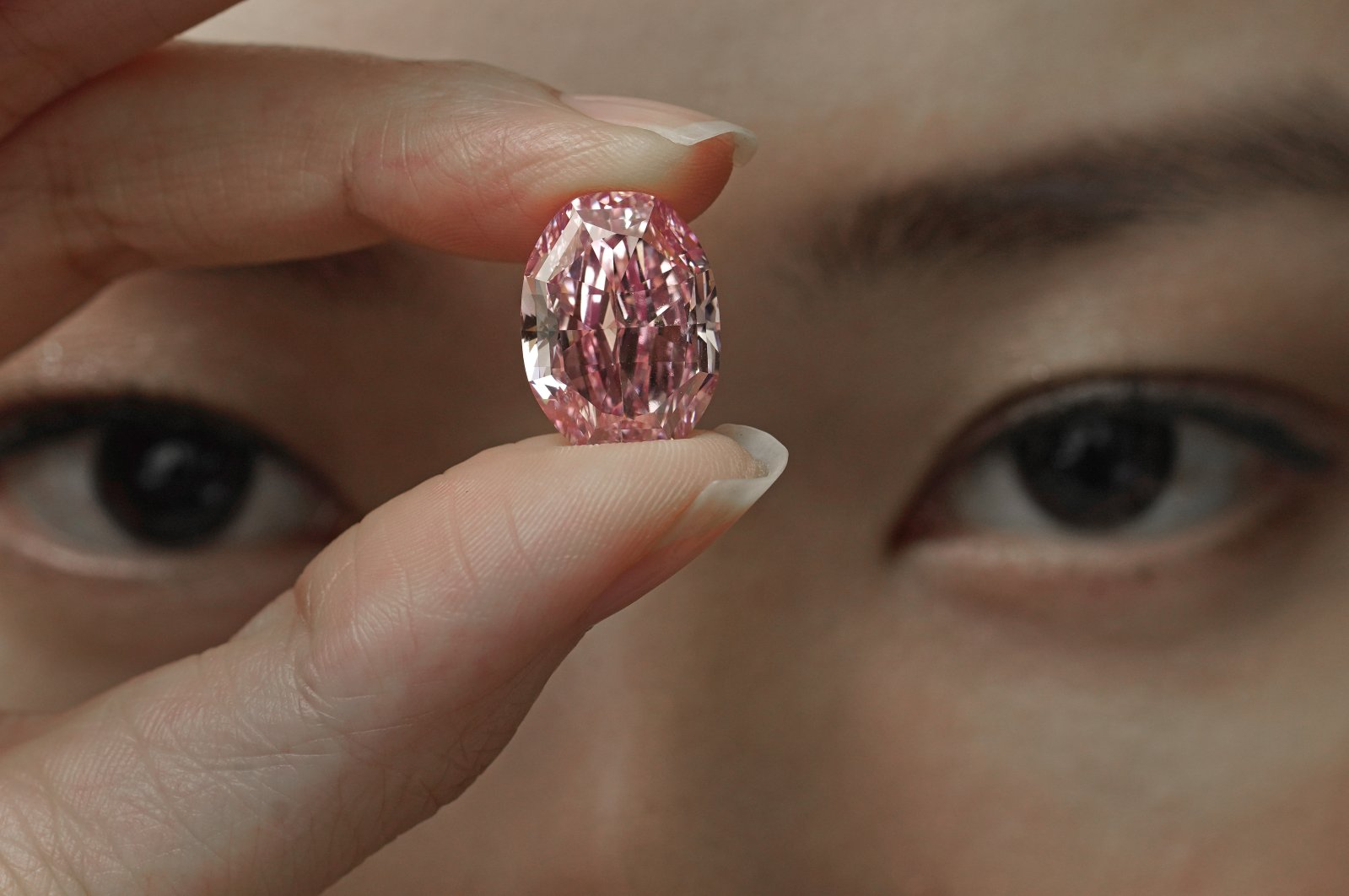 A model displays an ultra-rare 14.83-carat diamond that is one of the largest internally flawless fancy vivid purple-pink gem ever graded by the Gemological Institute of America at a Sotheby's auction room in Hong Kong on Oct. 12, 2020. (AP Photo)