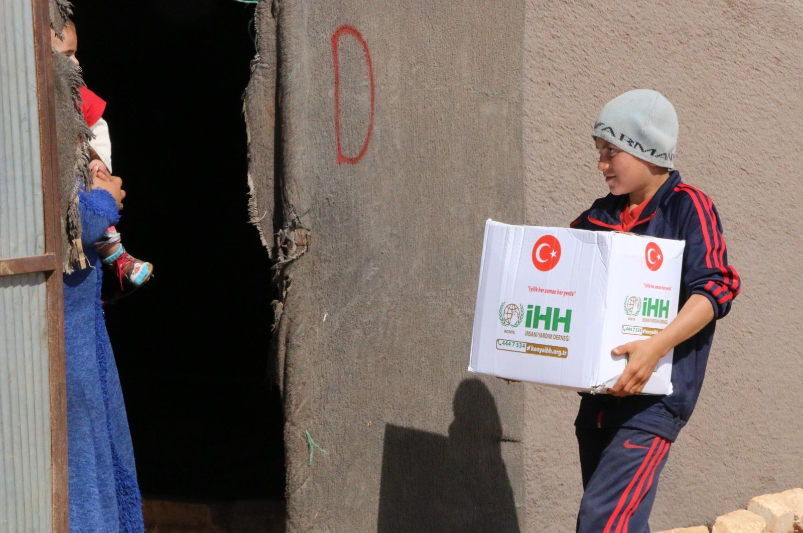A boy carries a box of food from the Humanitarian Relief Foundation (IHH), which distributed the packages to families in need in Syria's northwestern Idlib province, Oct. 13, 2020. (DHA Photo)