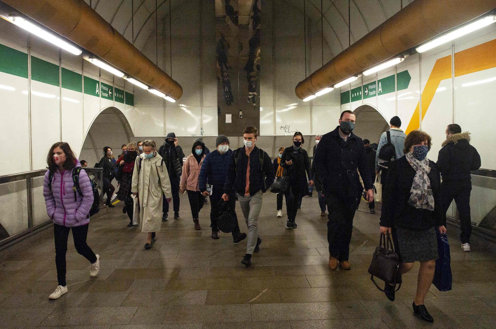 Passengers wearing masks walk in the corridor of a metro station in Prague, Oct.13, 2020. (AFP)
