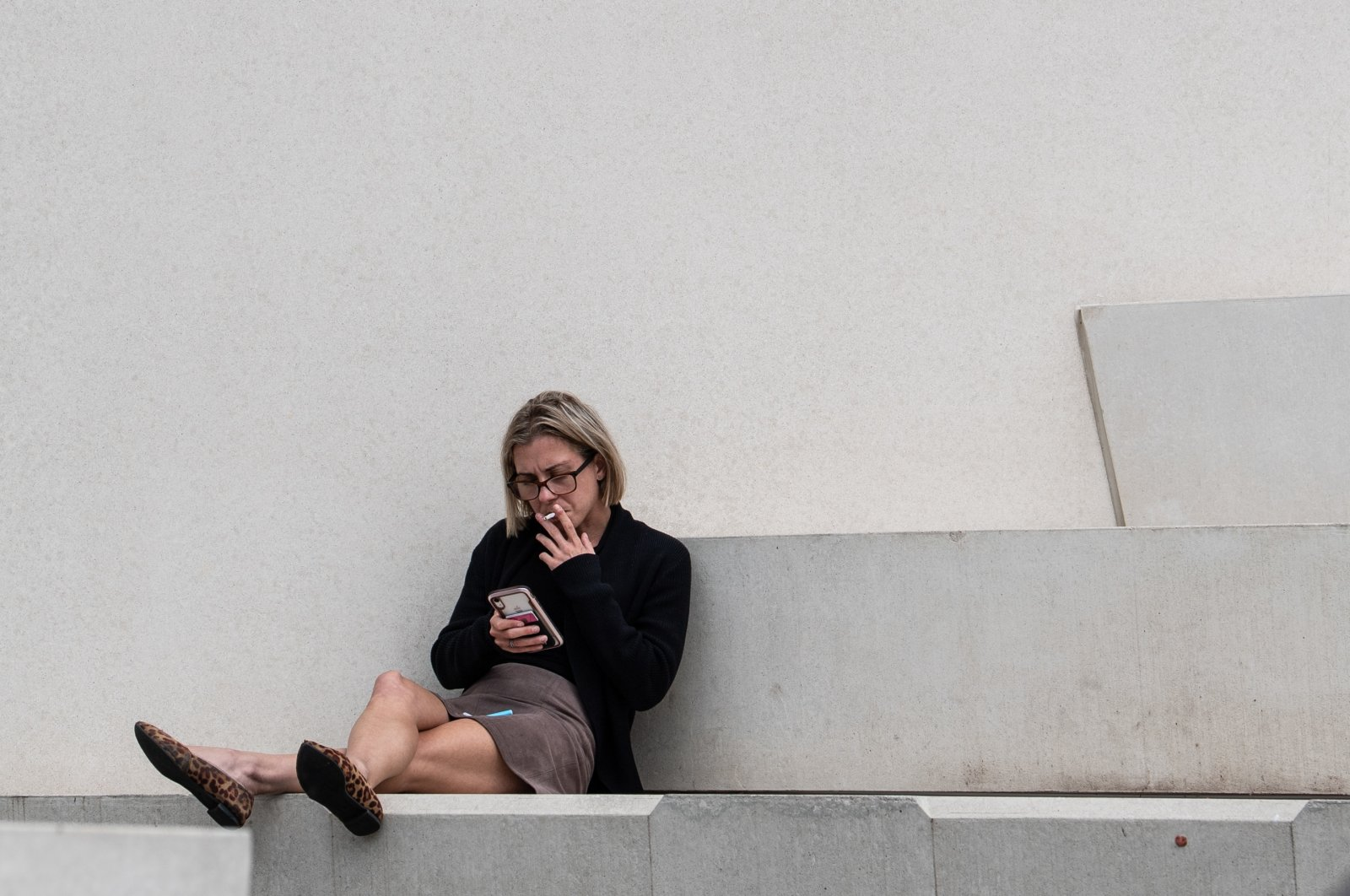 A woman smokes on steps in Campbells Cove, Sydney, Australia, March 16, 2020. (AAP Image via Reuters)