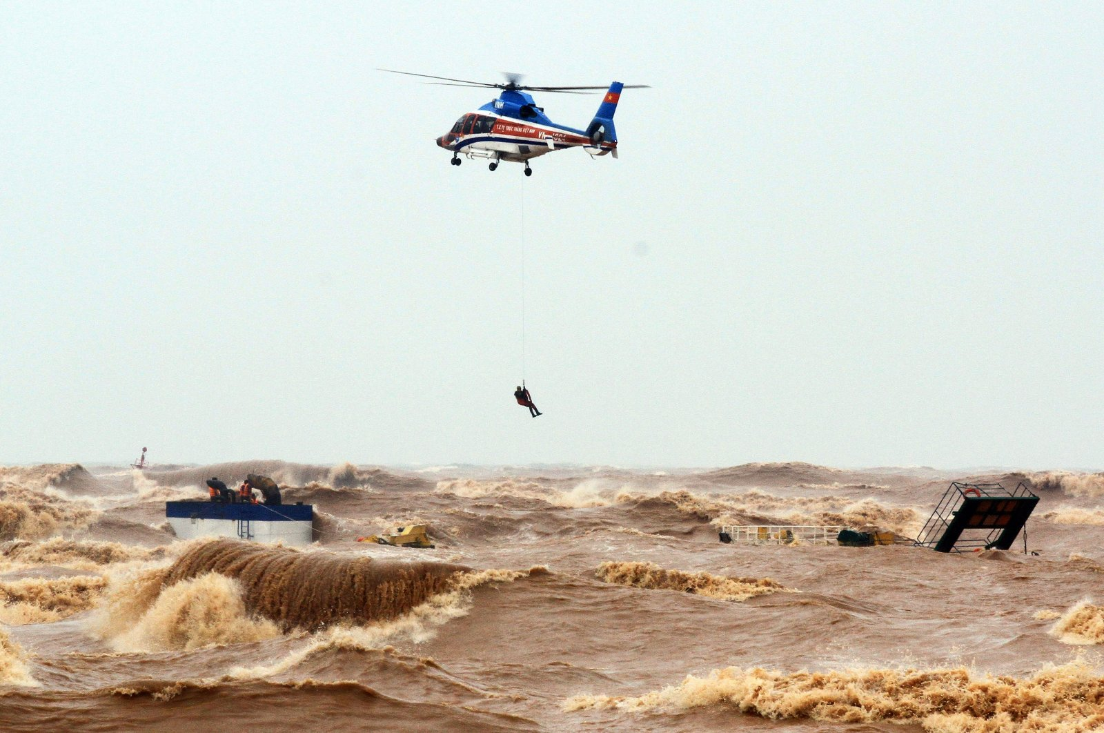 A defense ministry helicopter rescues stranded crew members at sea, Quang Tri province, Vietnam, Oct. 11, 2020. (EPA Photo)
