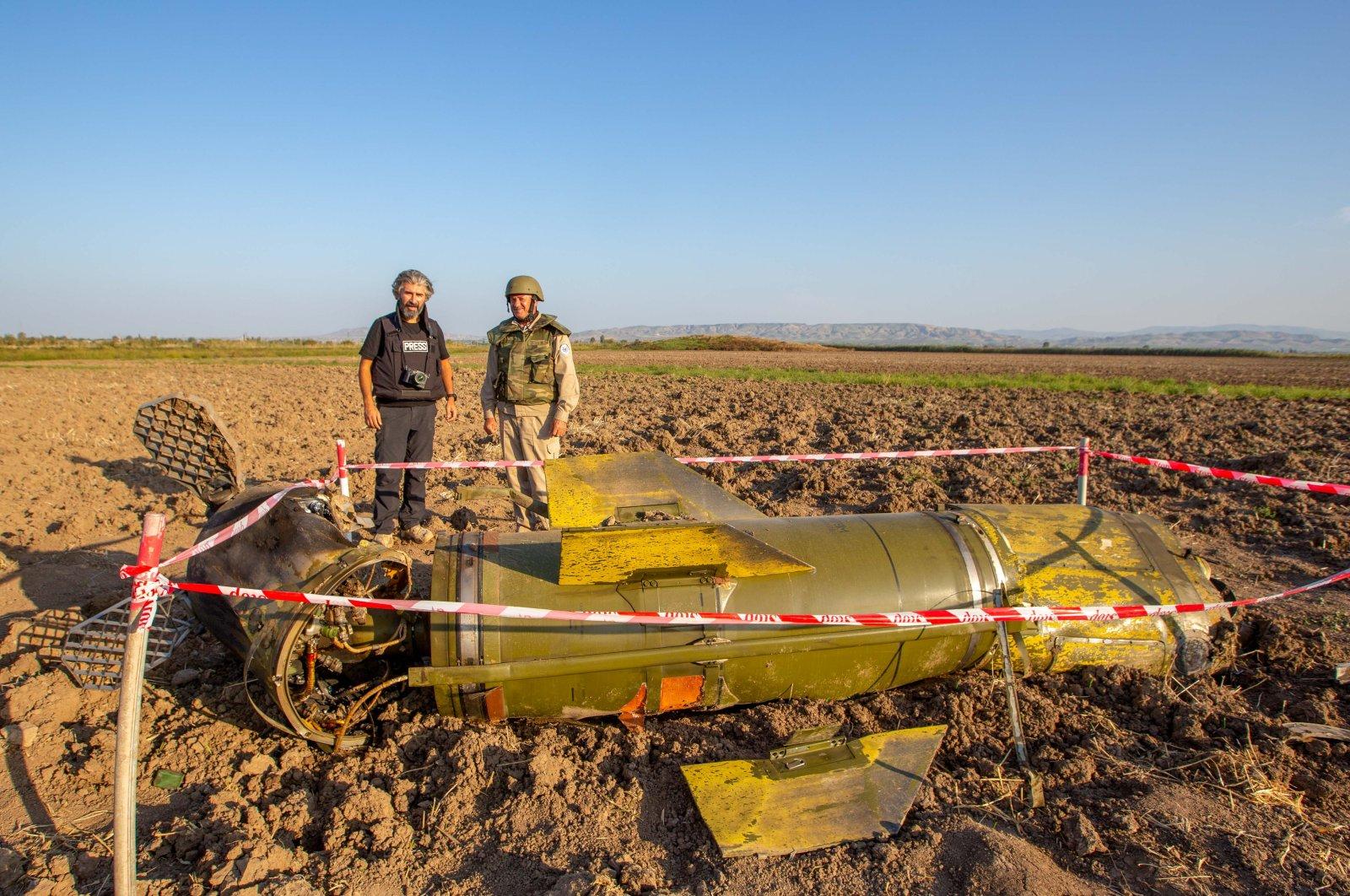 De-mining expert Azer Huseyinov stands in front of a Tochka-U missile with Sabah daily reporter Uğur Yıldırım in the town of Fuzuli, Azerbaijan, Oct. 12, 2020. (Rıza Özel Photo)