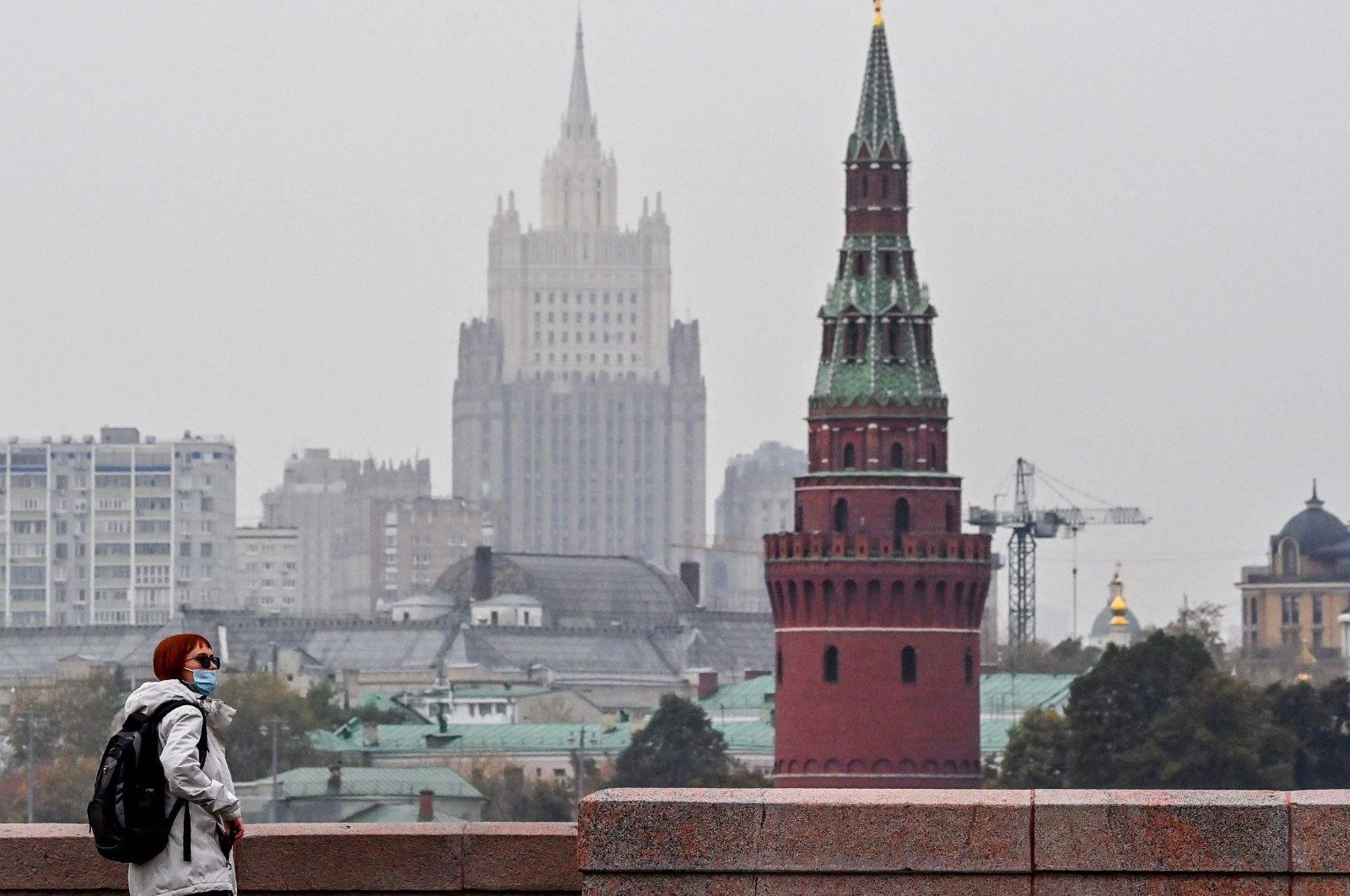 A woman wearing a face mask to protect against the coronavirus disease walks along a bridge in front of a tower of the Kremlin and the Russian Foreign Ministry building in the background in central Moscow on Oct. 13, 2020. (AFP Photo)