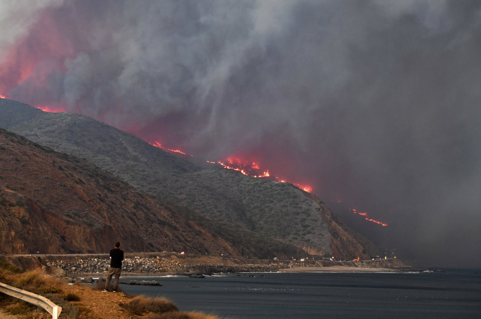 A man watches as the Woolsey Fire reaches the ocean along the Pacific Coast Highway (Highway 1) near Malibu, California, Nov. 9, 2018. (AFP Photo)