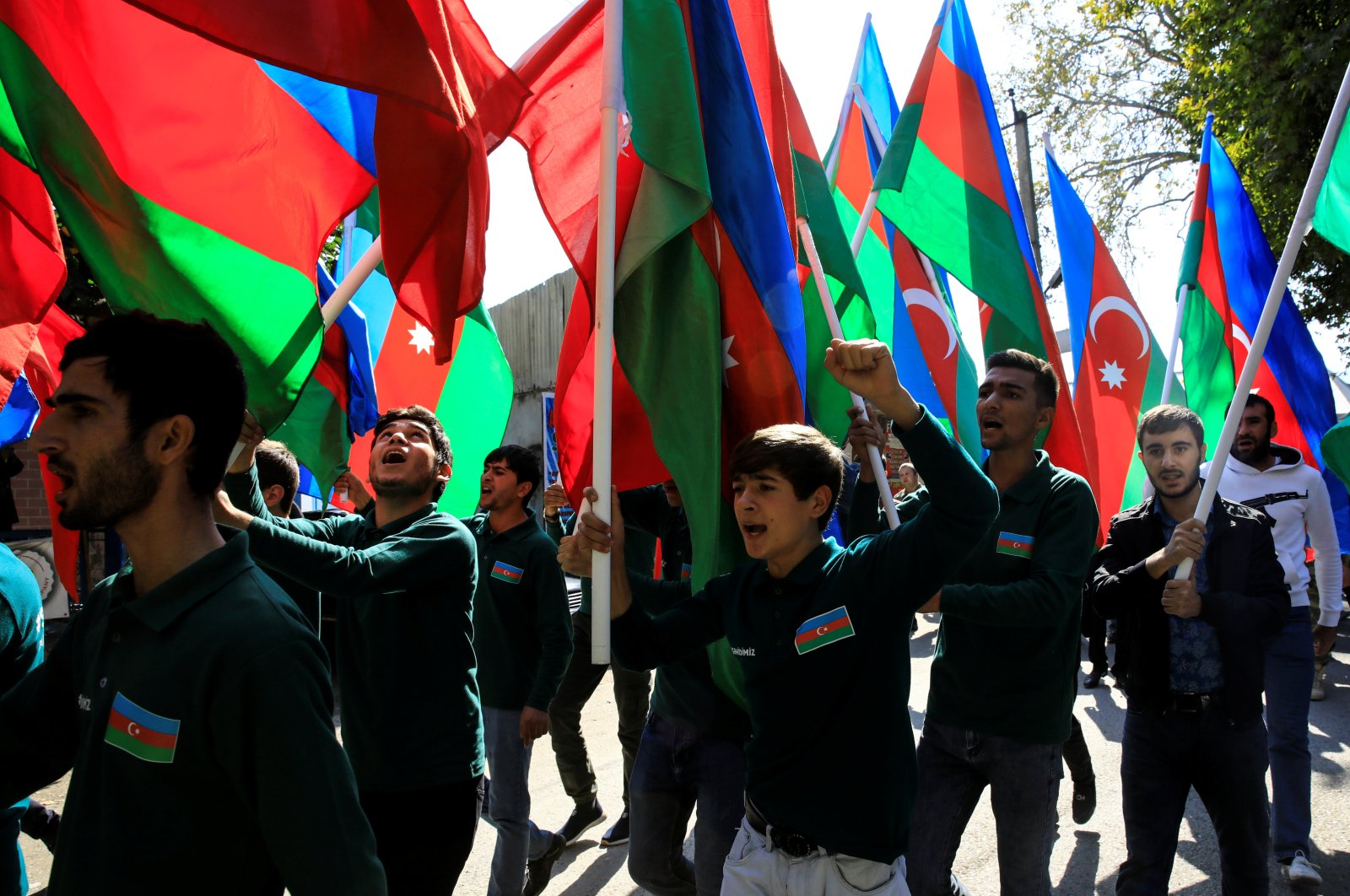 People hold Azerbaijan's national flags and shout slogans during the funeral of civilians killed in Ganja attack during the fighting over the occupied Nagorno-Karabakh region, in the city of Shamkir, Azerbaijan, Oct. 12, 2020. (REUTERS Photo)