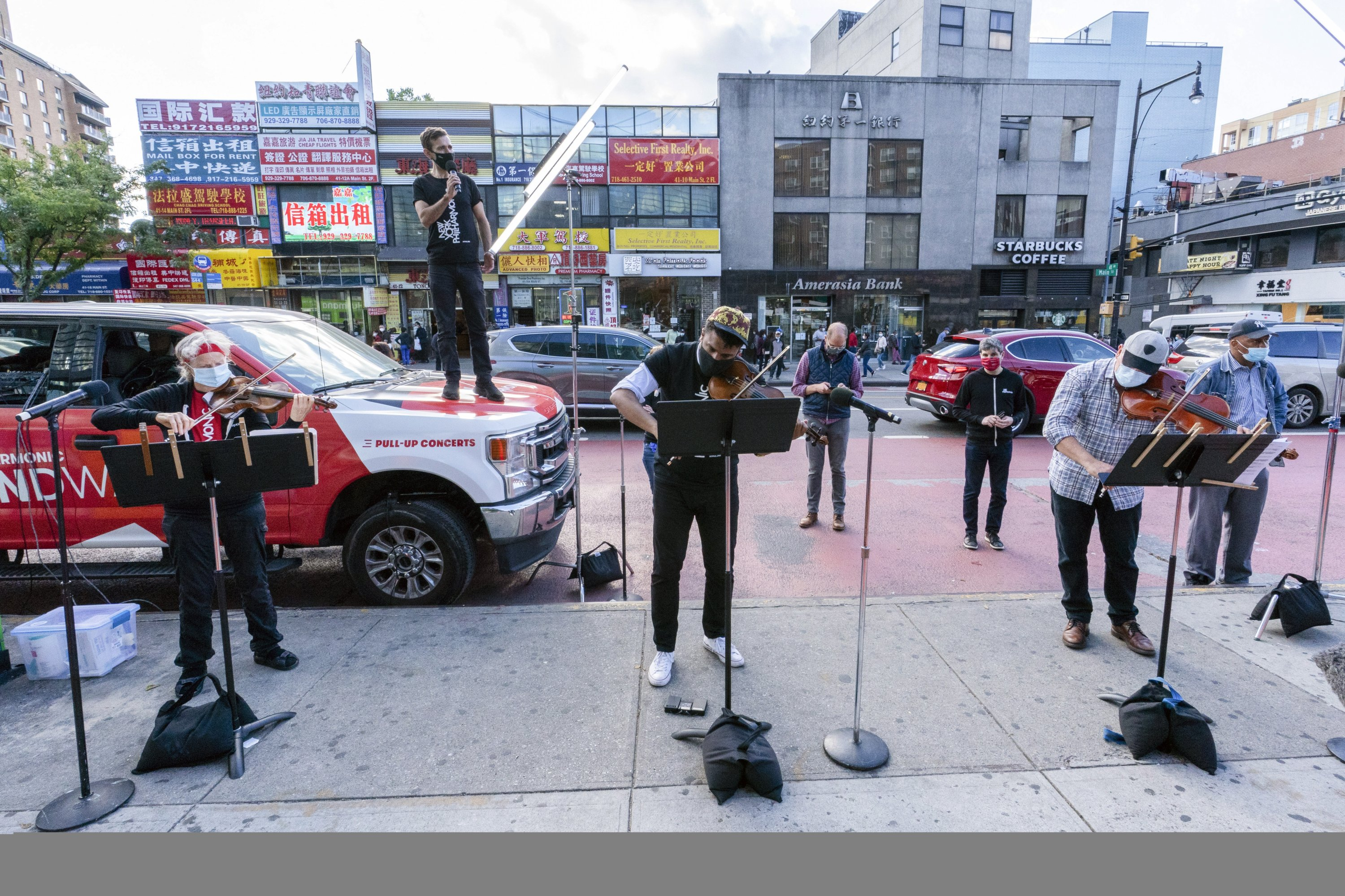 Members of the NY Phil Bandwagon (from L) violinist Fiona Simon, countertenor and producer Anthony Roth Costanzo, violinist Curtis Stewart and viola player Robert Rinehart perform in the Flushing neighborhood of the Queens borough of New York, Oct. 2, 2020. (AP PHOTO)