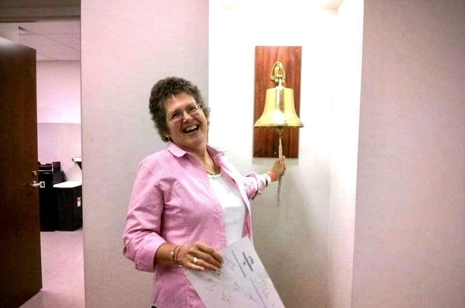 Jill Leach ringing the brass bell of triumph at the chemotherapy ward after completing her rounds of treatment. (Photo courtesy of Jill Leach)