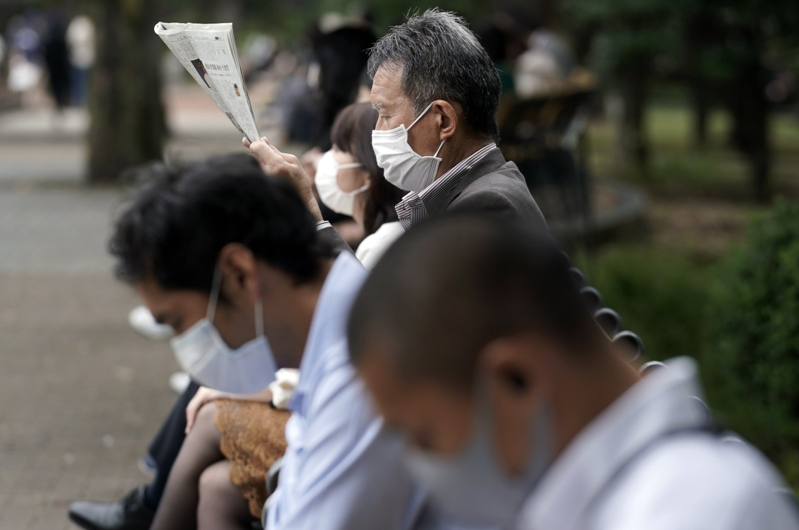 People wearing protective masks to help curb the spread of the coronavirus rest at a park, Oct. 14, 2020, in Tokyo. (AP Photo)