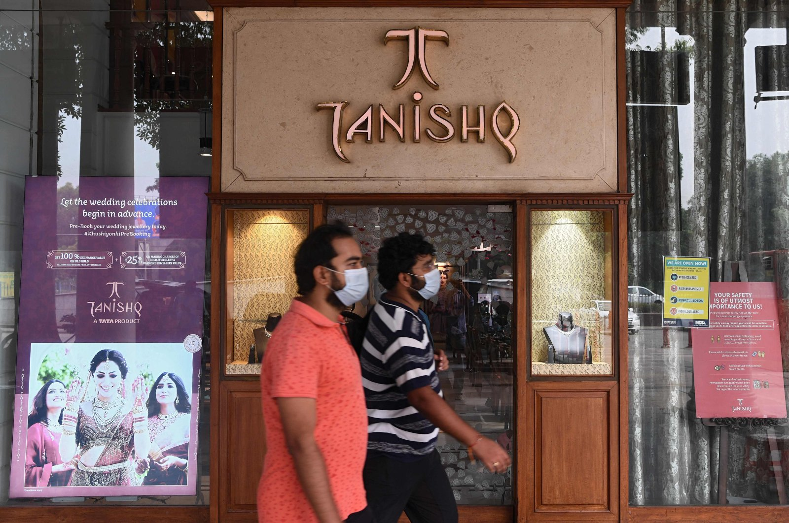 Men walk past a Tanishq jewelry showroom in a shopping arcade in New Delhi, India, Oct. 14, 2020. (AFP Photo)