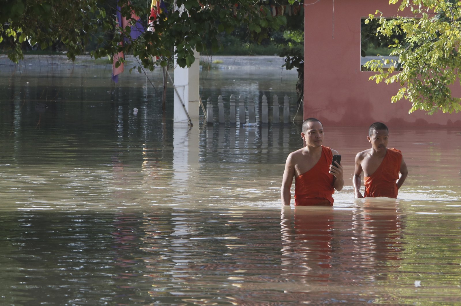 Buddhist monks walk through a flooded pagoda following recent rains on the outskirts of Phnom Penh, Cambodia, Oct. 14, 2020. (AP Photo)