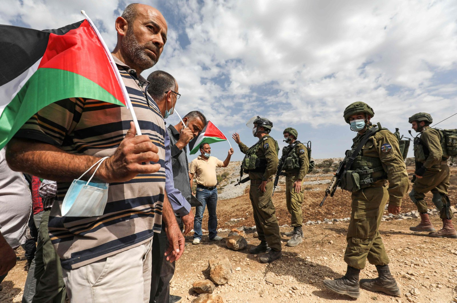 Palestinian protesters with flags, some mask-clad due to the COVID-19 pandemic, confront Israeli soldiers during a demonstration against illegal Jewish settlements in the town of Asira Shamaliya in the Israeli-occupied West Bank, near Nablus, Palestine, Oct. 9, 2020. (AFP Photo)