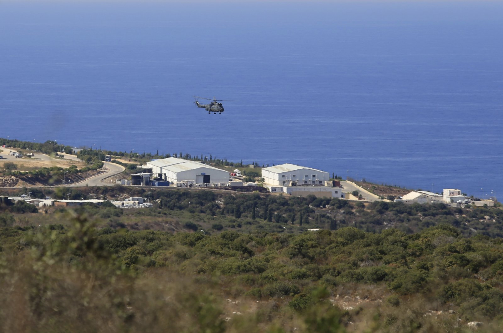 A helicopter flies over a base of the U.N. peacekeeping force, in the southern town of Naqoura, Lebanon, Oct. 14, 2020. (AP Photo)