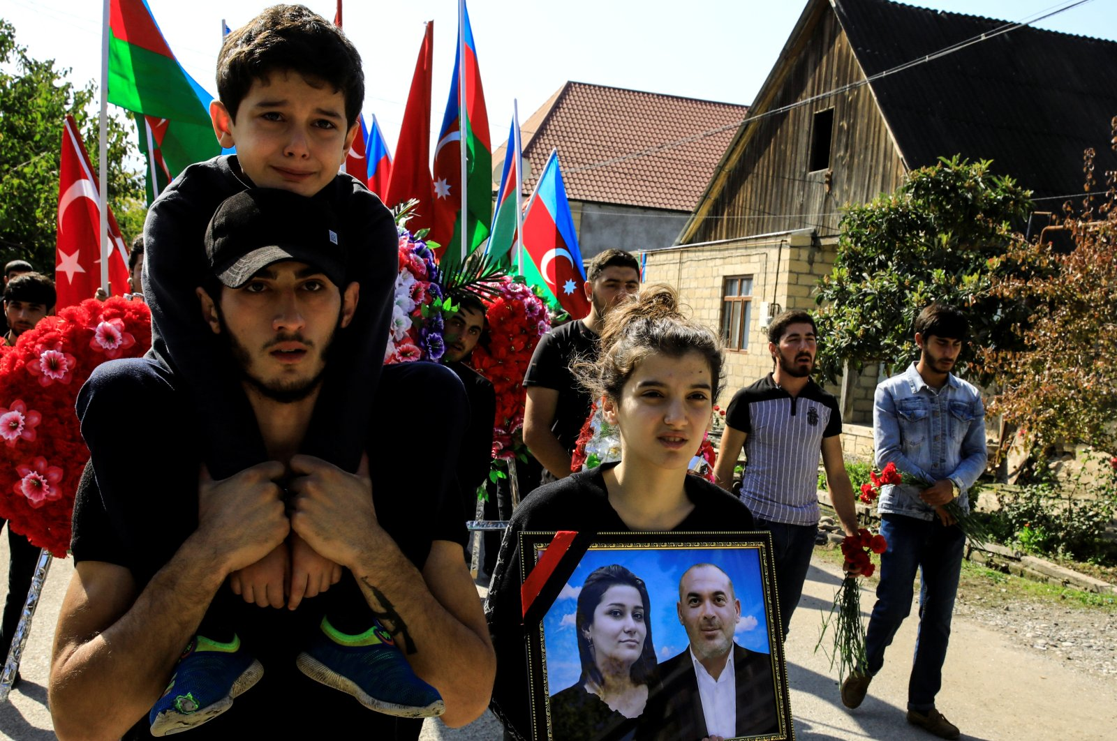 Sevil Aliyeva carries the portraits of her parents Anar Aliyev and Nurcin Aliyeva who were killed in Ganja attack as her brother Huseyin Aliyev cries on the shoulders of a relative during their funeral ceremony in the city of Shamkir, Azerbaijan, Oct. 12, 2020. (REUTERS)