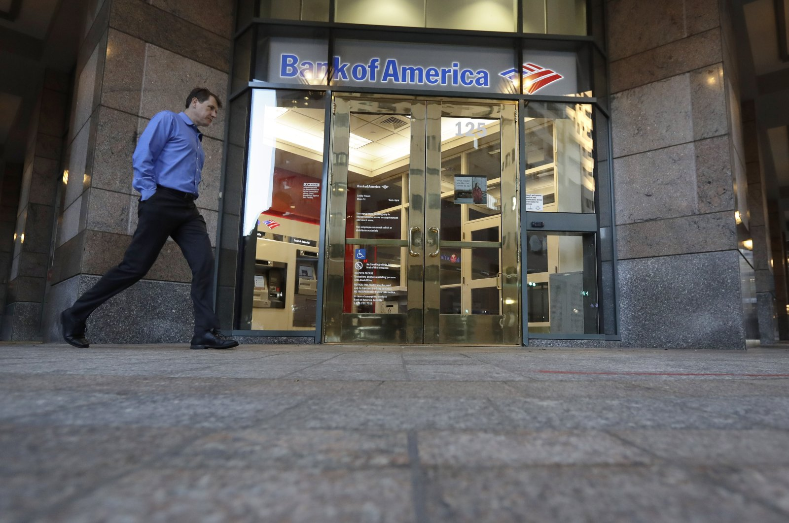 A passerby walks past the entrance to a Bank of America ATM, in Boston, Oct. 14, 2019. (AP Photo)