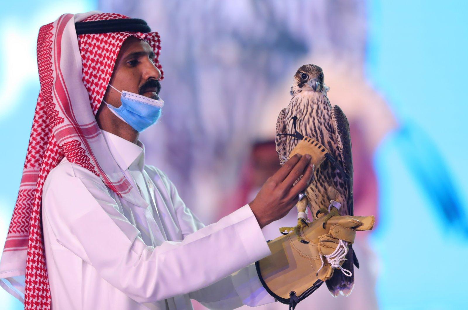 A man displays a falcon which was sold for $173,000 during Saudi Falcons Club Auction in King Abdulaziz Festival in Mulham, north of Riyadh, Saudi Arabia, Oct. 13, 2020. (Media Center Saudi Falcons Club Auction via Reuters)